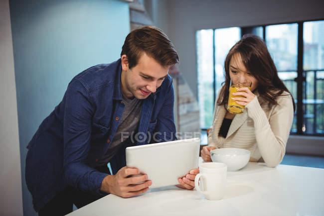 Casal usando tablet digital enquanto toma café da manhã em casa — Fotografia de Stock