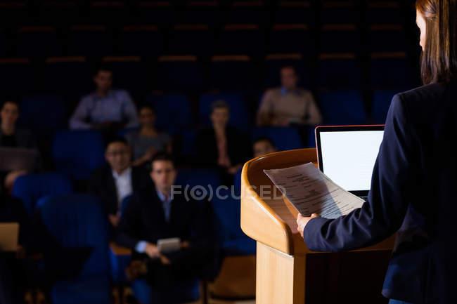 Vista posteriore di affari femminile dando un discorso al conference center — Foto stock