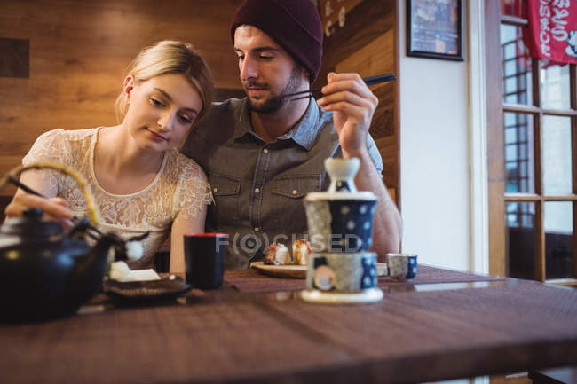 Couple romancing while having sushi in restaurant — Stock Photo
