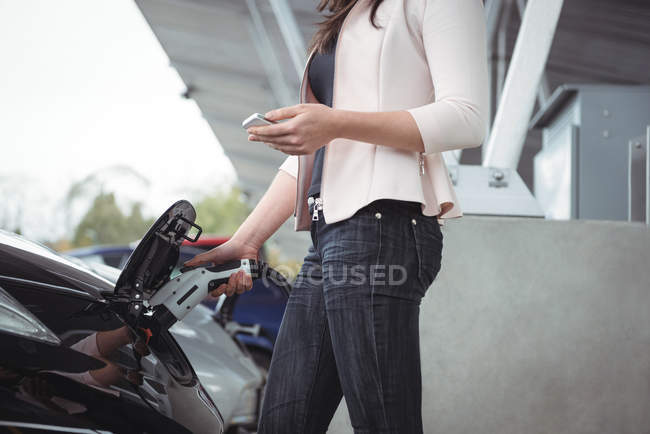 Mid section of woman using mobile phone while charging electric car vehicle charging station — Stock Photo