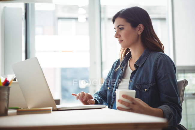 Business executive using laptop while having cup of coffee in office — Stock Photo