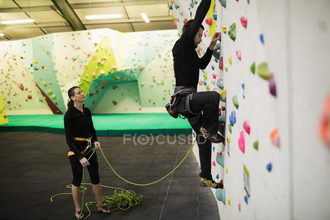 Trainer assisting man while climbing on artificial wall in gym — Stock Photo
