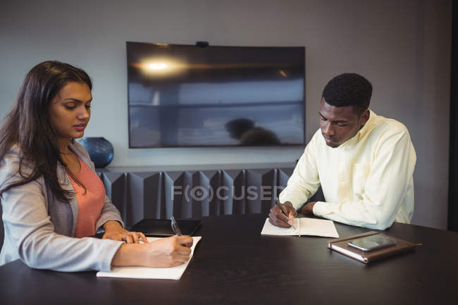 Businesswoman and colleague writing in a diary in conference room at office — Stock Photo