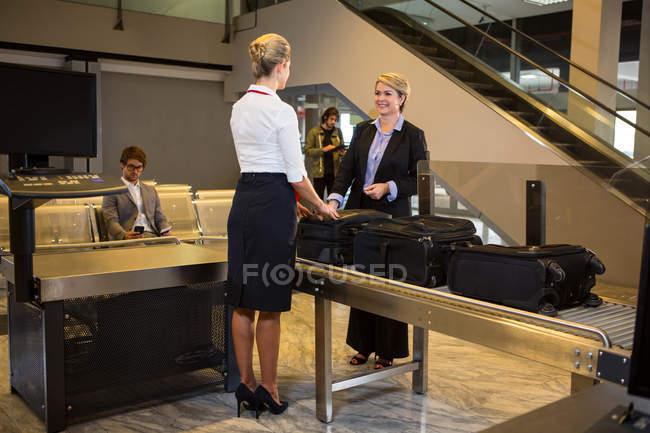 Empresaria interactuando con el personal del aeropuerto con el equipaje guardado en la cinta transportadora en la terminal del aeropuerto - foto de stock