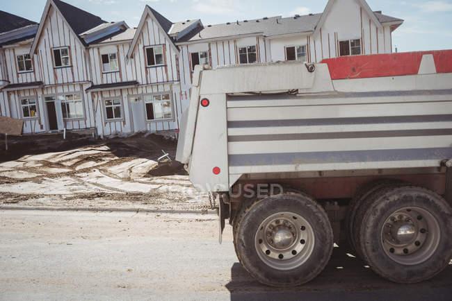 Самоскид на будівельному майданчику з будівництвом у фоновому режимі — стокове фото
