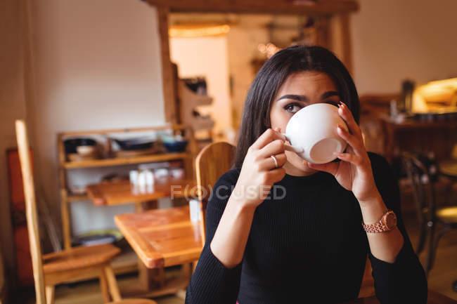 Donna che beve caffè in caffetteria — Foto stock