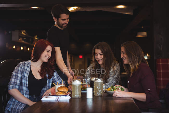 Щасливі подруг, насолоджуючись їжі у барі, а офіціант, подачі їжі — стокове фото