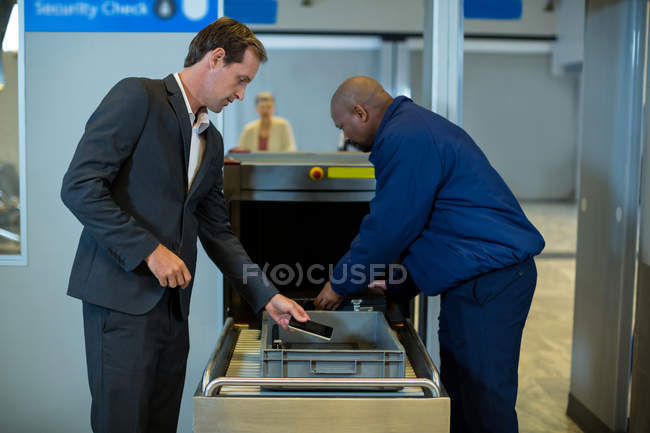 Airport security officer checking luggage of commuter in airport terminal — Stock Photo