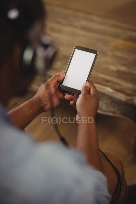 Man listening to music on mobile phone in living room at home — Stock Photo