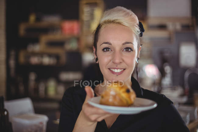 Portrait of waitress holding plate with muffin in cafe — Stock Photo