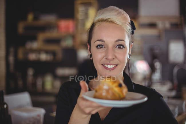 Retrato de garçonete, segurando o prato com bolinho no café — Fotografia de Stock