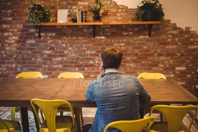 Rear view of man talking on mobile phone in cafe — Stock Photo