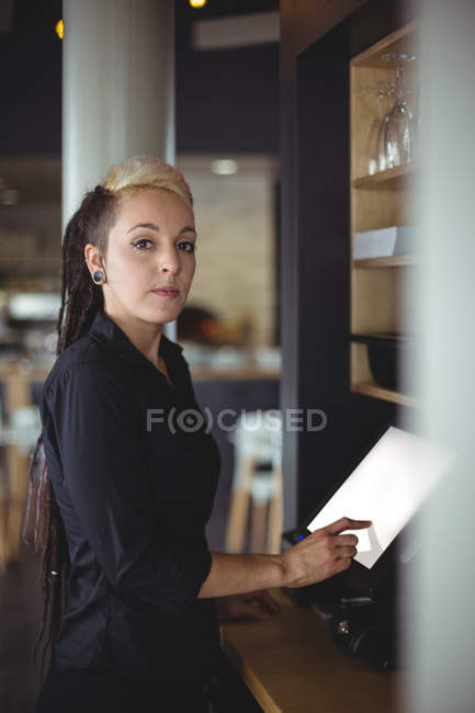 Portrait of waitress using cash register at counter in cafe — Stock Photo
