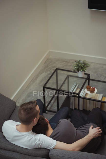High angle view of romantic gay couple embracing on sofa at home — Stock Photo