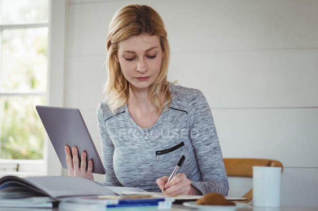 Beautiful woman writing in diary while using digital tablet in living room at home — Stock Photo