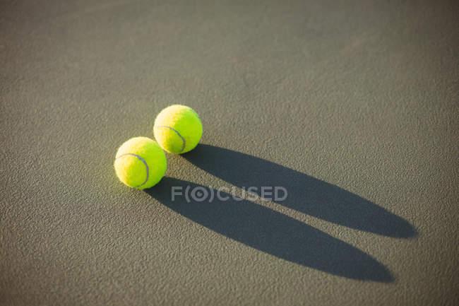 Primer plano de pelotas de tenis en corte en la luz del sol - foto de stock