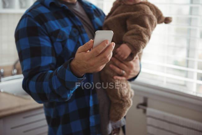 Средняя часть отца с помощью мобильного телефона, держа ребенка на кухне — стоковое фото