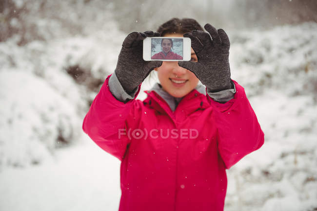 Smiling woman taking selfie on mobile phone during winter — стоковое фото