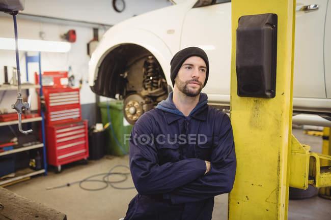 Mecánico de pie con los brazos cruzados en garaje de reparación - foto de stock