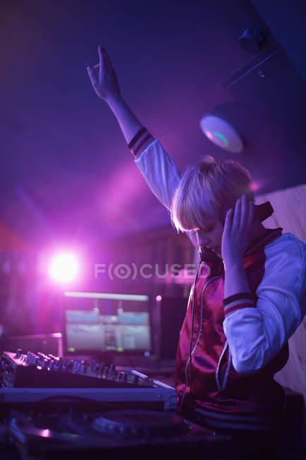 Pretty female dj with arm raised while playing music in bar — Stock Photo