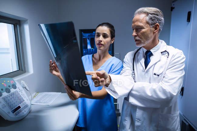 Médico y enfermera examen de rayos x en hospital - foto de stock