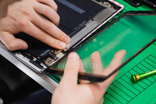 Nahaufnahme eines Mannes, der den Bildschirm eines digitalen Tablets im Reparaturzentrum repariert — Stockfoto