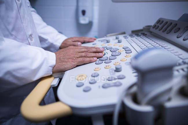 Mid section of surgeon operating ultrasonic device machine at hospital — Fotografia de Stock