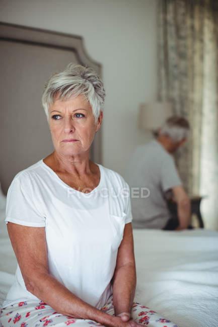 Besorgte und nachdenkliche Seniorin sitzt im Schlafzimmer — Stockfoto