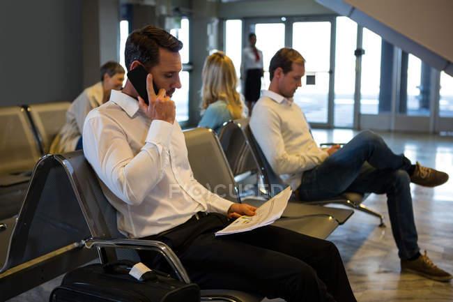 Uomo d'affari che parla al cellulare in sala d'attesa al terminal dell'aeroporto — Foto stock