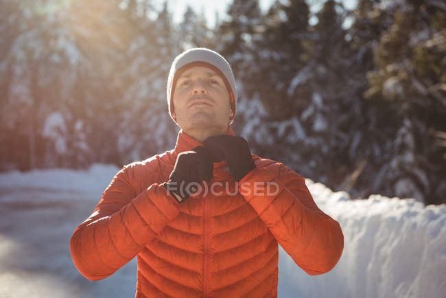 Man removing warm clothing in forest during winter — Stock Photo