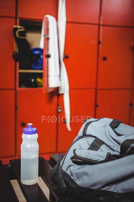 Primo piano della bottiglia d'acqua e della borsa nello spogliatoio — Foto stock