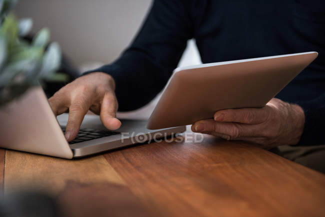 Mid-section of man using laptop in living room at home — Stock Photo