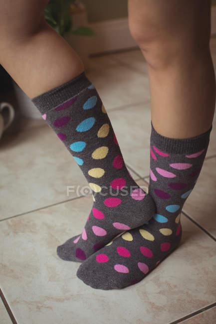 Женские ноги в разноцветных горошек горошек носки дома — стоковое фото