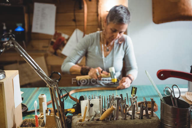 Mature craftswoman hammering leather in workshop interior — Stock Photo