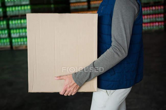 Sezione media del lavoratore che trasporta scatola di cartone in magazzino — Foto stock