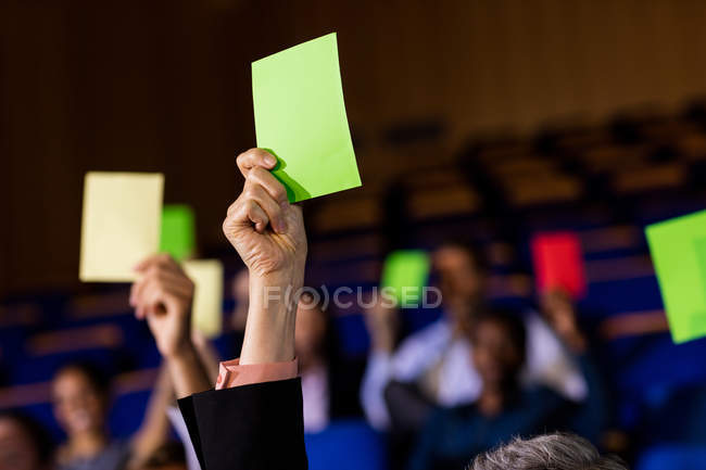 Business executives showing approval by raising hands at conference center — Stock Photo