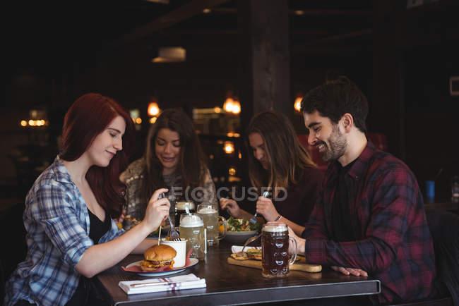 Щасливі друзів, насолоджуючись їжі в м. бар — стокове фото