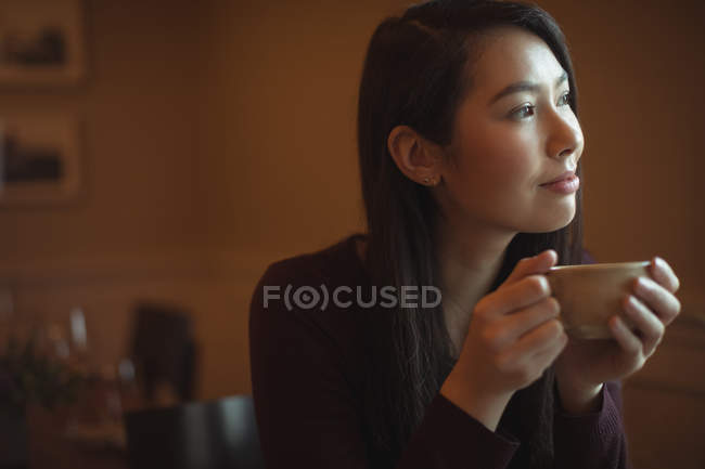 Thoughtful woman having cup of coffee in cafe — Stock Photo