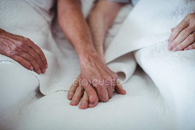 Close-up of senior couple holding hands on bed — Stock Photo