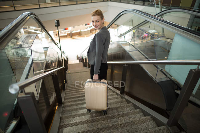 Business woman standing on escalator with luggage at airport — Stock Photo