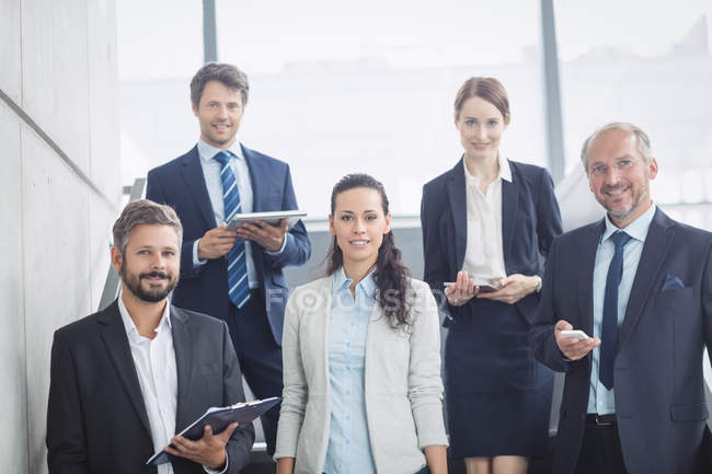 Portrait of confident business people standing on staircase in office — Stock Photo