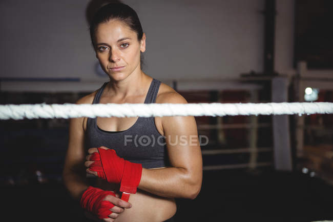 Portrait of female boxer wearing red strap on wrist in fitness studio — Stock Photo