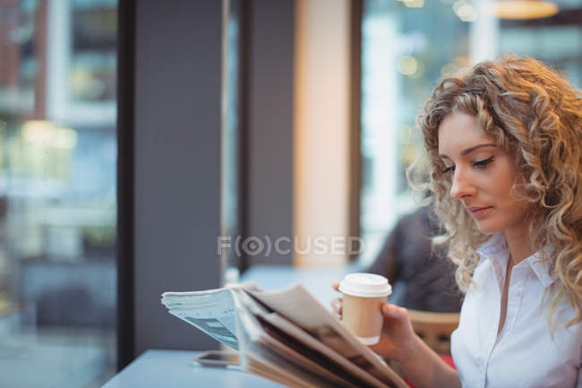 Thoughtful businesswoman reading newspaper with coffee at counter in cafeteria — Stock Photo