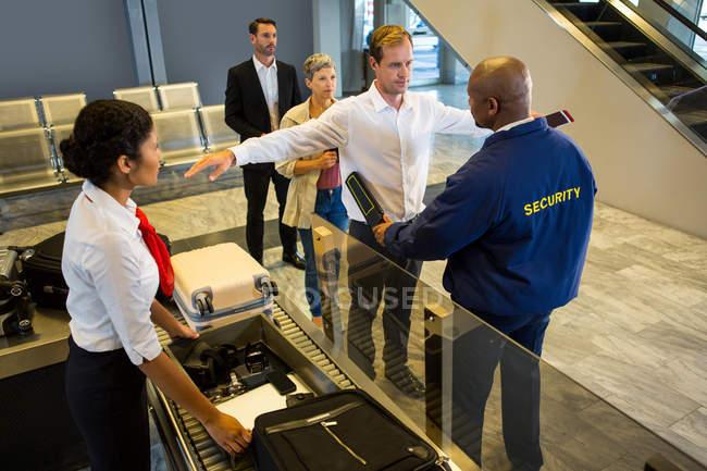 Un agent de sécurité fouille les passagers avec un détecteur de métaux à l'aérogare — Photo de stock