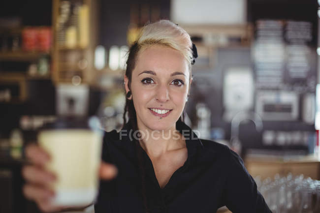 Portrait of waitress standing with disposable coffee cup in cafe — Stock Photo