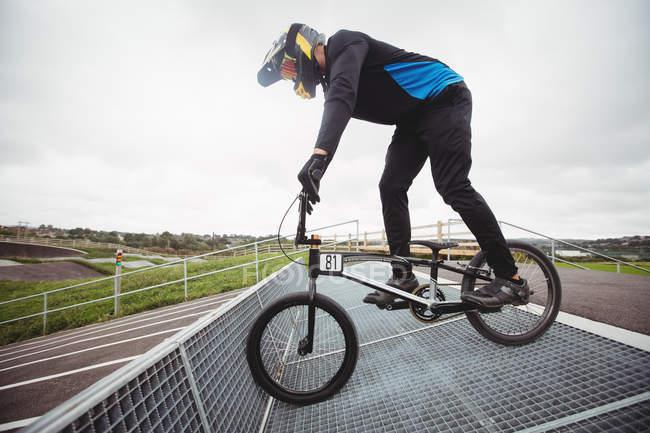 Велогонщик готовится к гонкам BMX на старте пандуса в скейтпарке — стоковое фото