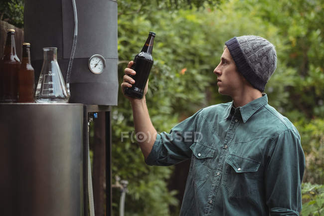 Man holding beer bottle while making beer at home brewery — Foto stock