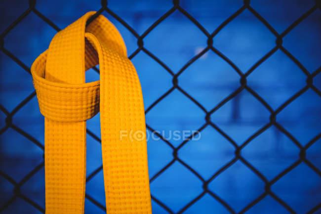 Крупный план желтого пояса карате, висящего на сетке ограждения в фитнес-студии — стоковое фото