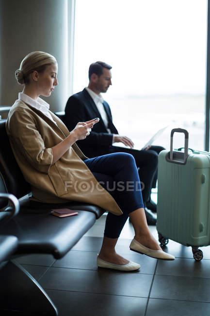 Женщина с мобильного телефона в зоне ожидания в терминале аэропорта — стоковое фото