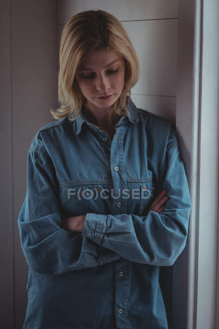 Mulher tensa de pé com os braços cruzados em casa — Fotografia de Stock